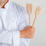 Male chef holding kitchen utensils with crossed arms in uniform , front view.