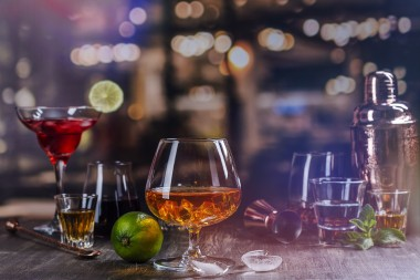 Glass of cognac or whiskey on a bar counter. Assortment of different strong alcohol drinks over night lights background. Copy space