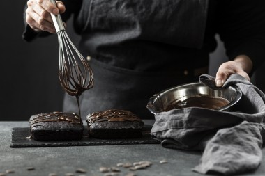 front-view-of-pastry-chef-preparing-cake-with-chocolate